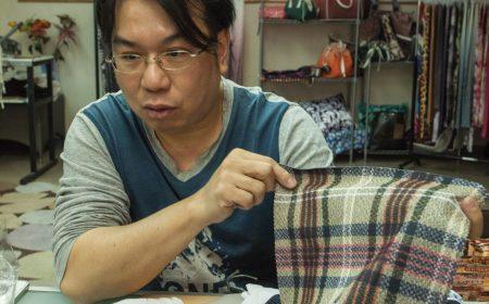 老闆陸達明先生正展示數碼印花印在不同質料的成品。